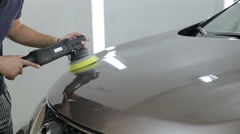 Worker polishing bonnet of car Stock Footage
