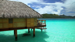Overwater luxury Bungalows in tropical Aquamarine lagoon a Tahitian hotel resort Stock Footage