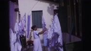 1967: african american women doing laundry outside clothesline hanging sheets Stock Footage