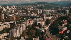 View Sochi southern city from a height, visible buses, cars, buildings, mountain Stock Footage