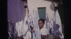 1967: smiling lady hanging clothes out to dry near house in the warm summer Stock Footage