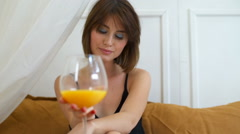 Beautiful woman posing with a glas of orange juice in bed Stock Footage