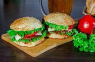 Beer and homemade burgers buns with beef patties  fresh salad ingredients Stock Photos