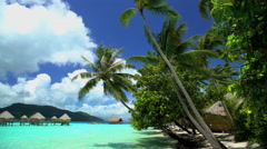 Beach Palm trees Overwater Bungalows in tropical aquamarine lagoon a luxury Stock Footage