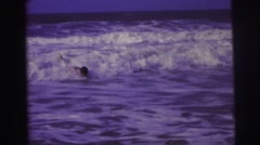1967: teenage boy body surfing in the ocean close to shore on beautiful day Stock Footage