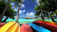 Canoe boats Palm trees Overwater Bungalows in tropical aquamarine lagoon a Stock Footage