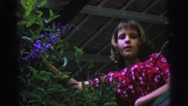 1967: young teenage girl with purple flower bush plant BRAZIL Stock Footage