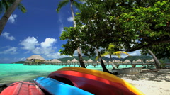 Kayak boats Palm trees by Overwater Bungalows in tropical aquamarine lagoon a Stock Footage