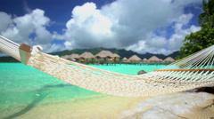 Beach hammock Overwater Bungalows in tropical aquamarine lagoon a luxury Stock Footage