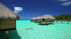Overwater luxury Bungalows in tropical Aquamarine lagoon a Tahitian vacation Stock Footage