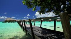 Palm trees Overwater walkway luxury Bungalows in tropical Aquamarine lagoon Stock Footage