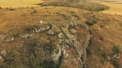 Aerial view of training by boy on golden stone rock Stock Footage