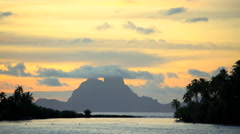 Cloudscape view at sunset of tropical Bora Bora Island lagoon and Mt Otemanu in Stock Footage