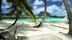 A hammock on a tropical beach by overwater bungalows set in aquamarine lagoon Stock Footage