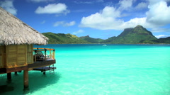 Mt Otemanu and overwater luxury bungalows in a tropical aquamarine lagoon Stock Footage