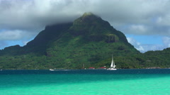 Aquamarine lagoon with a sail boat and Mt Otemanu in Tahitian vacation resort of Stock Footage