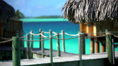 The boardwalk of a luxury overwater vacation bungalow set in an aquamarine Stock Footage