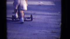 1946: toddler learns to ride scooter DETROIT, MICHIGAN Stock Footage