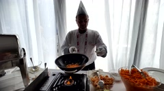 Chef prepares wok for dinner for participants of V Anniversary International Stock Footage