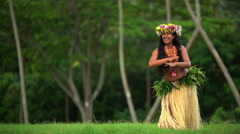 Polynesian graceful girl dancer in grass skirt and flower headdress dancing hula Stock Footage