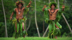 Polynesian young men in traditional grass skirts with flower headdress dancing Stock Footage