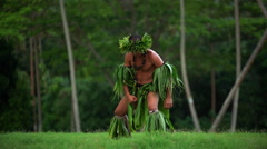 Barefoot Tahitian Polynesian man in hula skirts and flower headdress performing Stock Footage