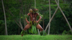 Polynesian young man in traditional grass skirts with flower headdress dancing Stock Footage