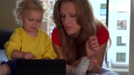 Cute toddler girl and her mom smile using tablet computer lying on sofa Stock Footage