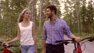 Smiling woman and handsome man walking together holding their bicycles Stock Footage