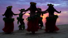 Polynesian men in warrior dress at sunset with girls in grass skirts and flower Stock Footage