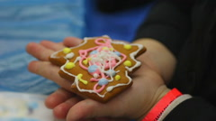 Child hands holding little ginger cookie in the shape of Christmas tree Stock Footage