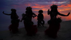 Barefoot Tahitian males in warrior dress on the beach at sunset with females  Stock Footage