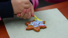Attentive child decorating star shaped gingerbread with confectionary glaze Stock Footage
