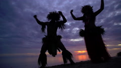 Polynesian man at sunset in warrior dress with girl in grass skirts and flower Stock Footage