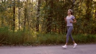 Young blond woman jogging fast in the forest and enjoying the views of nature Stock Footage