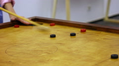 Two friends playing carrom game, strike and pocket table game, family tournament Stock Footage