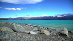 Natural turquoise color water of Lake Tekapo Mackenzie Basin with Southern Alps Stock Footage
