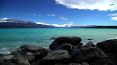 Waves over rocks on shoreline of scenic holiday destination Lake Tekapo Stock Footage