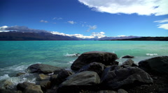 Scenic view of Southern Alps with waves over rocks on shoreline of Lake Tekapo Stock Footage