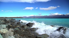 Natural beauty of turquoise water and waves over rocks on Lake Tekapo Mackenzie Stock Footage