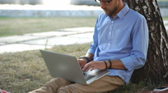 Handsome hipster using laptop in park on a summers day Stock Footage
