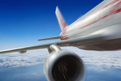 Commercial jet flies very fast in blue sky Stock Photos