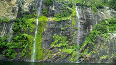 Scenic mountain side waterfalls and vegetation in Milford Sound Piopiotahi Stock Footage