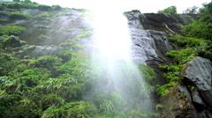 Waterfall over mountain cliff in valley of Milford Sound Piopiotahi Fiordland Stock Footage