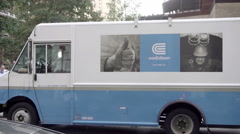 Con Edison truck parked city street, panning man riding bicycle and food truck Stock Footage