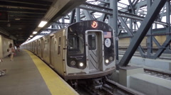 F Train pulling into elevated outdoor subway station in slow motion NYC Stock Footage