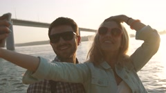 Smiling couple making pictures of themselves against sunshine background Stock Footage