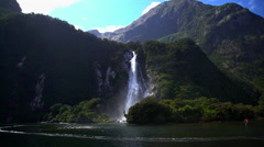 Mountain side waterfall in UNESCO World Heritage Site Milford Sound Piopiotahi Stock Footage