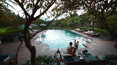 Family enjoys eternity pool with lush gardens surrounding it Stock Footage