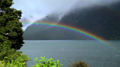 UNESCO World Heritage Site Fiordland National Park with rainbow over mountain Stock Footage